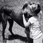 child hugging black great dane